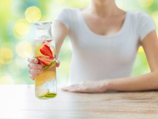 Женщина держит бутылку с напитком